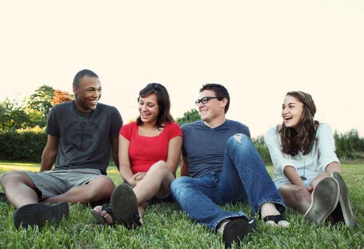 smiling women and men sitting on green grass